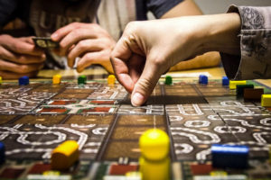 The hands of two individuals playing a board game.